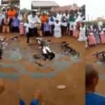 Pastor stirs controversy as he rolls in engine oil, while members spray money on him during church crusade